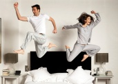 Couple leaping out of bed